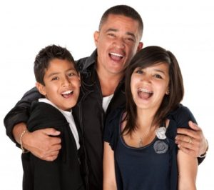 smiling man with arms around boy and girl