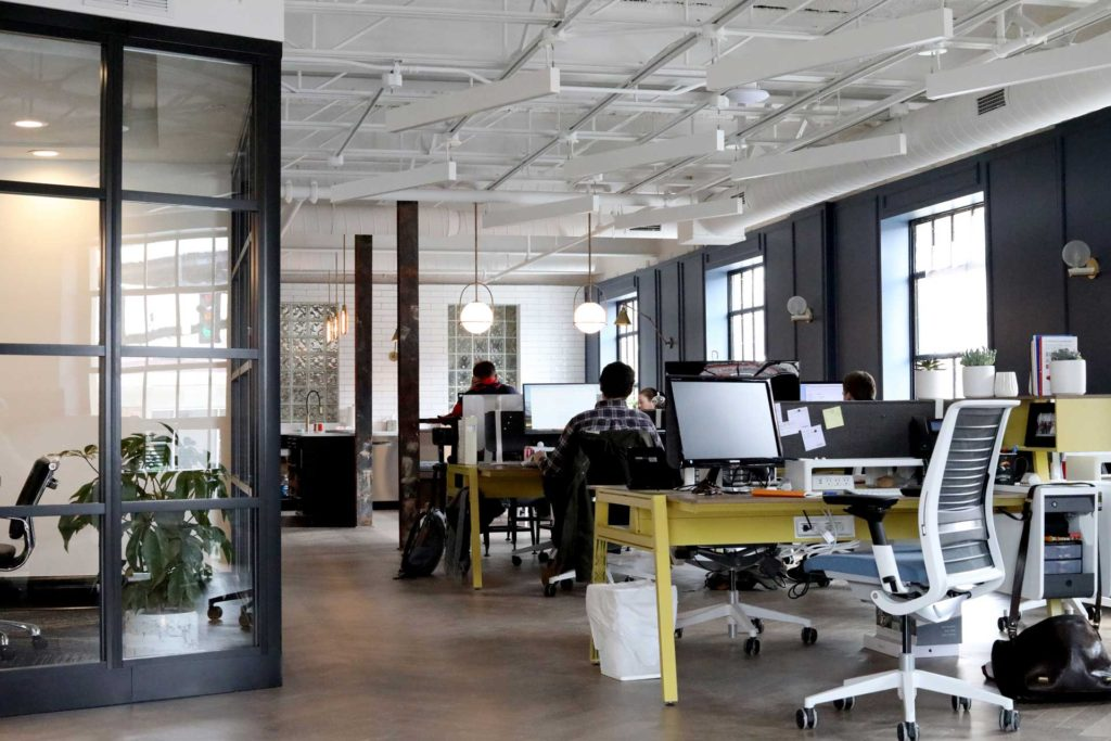 modern work space with rows of yellow desks and computers