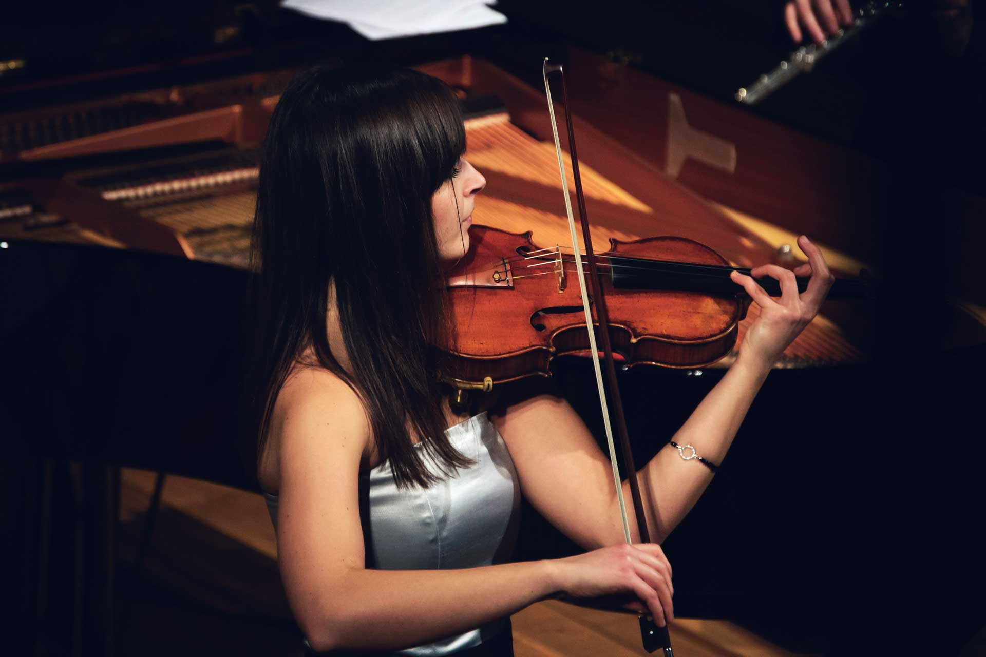 young woman in grey dress playing the violin in front of piano