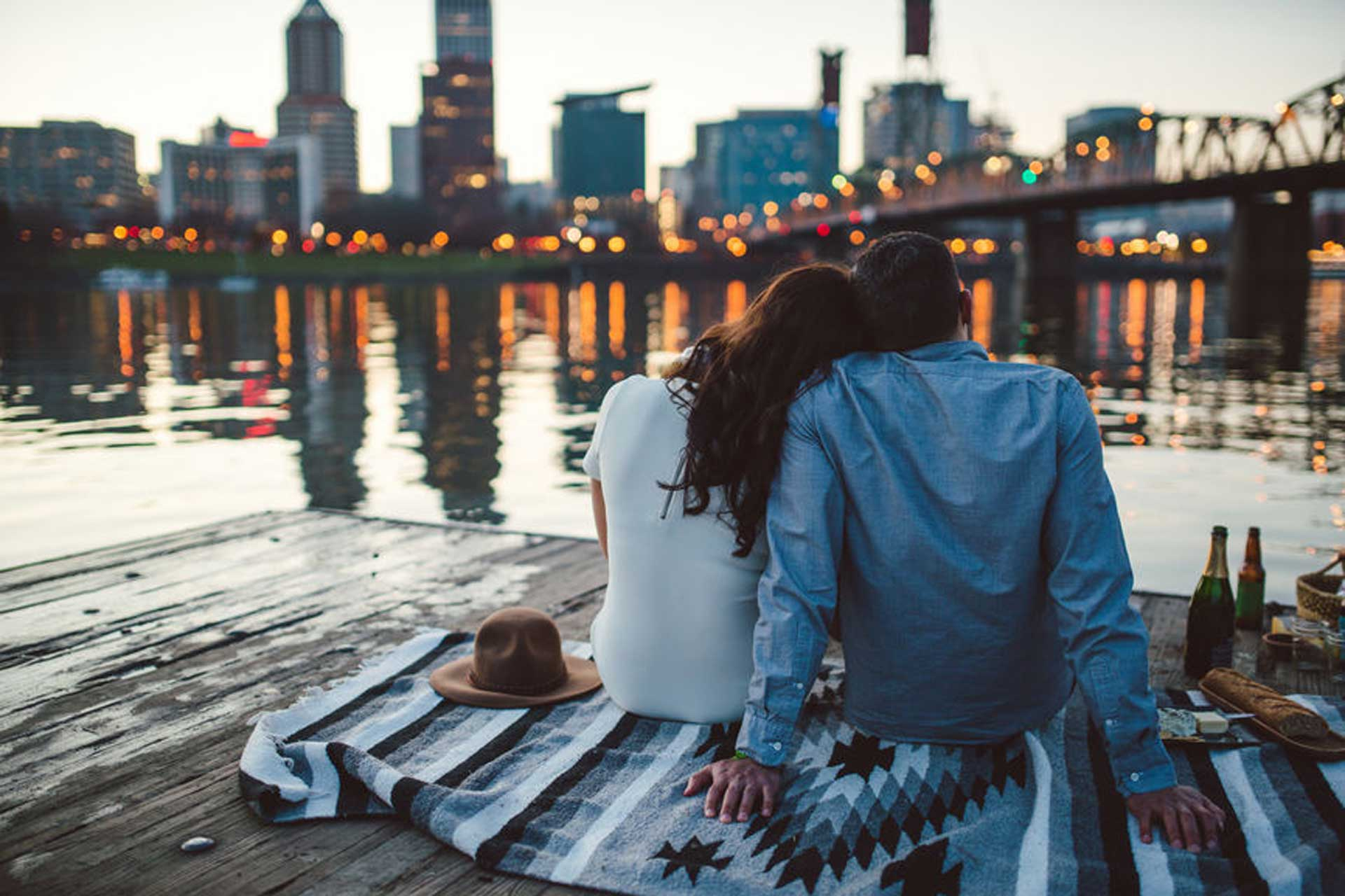 couple sitting on blanket in front of lake with city skyline and bridge in the background