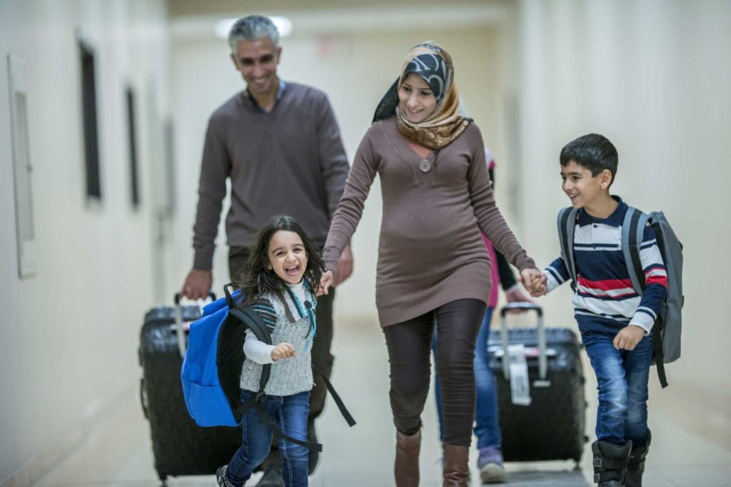 smiling family of four walking down hallway with suitcases and backpacks