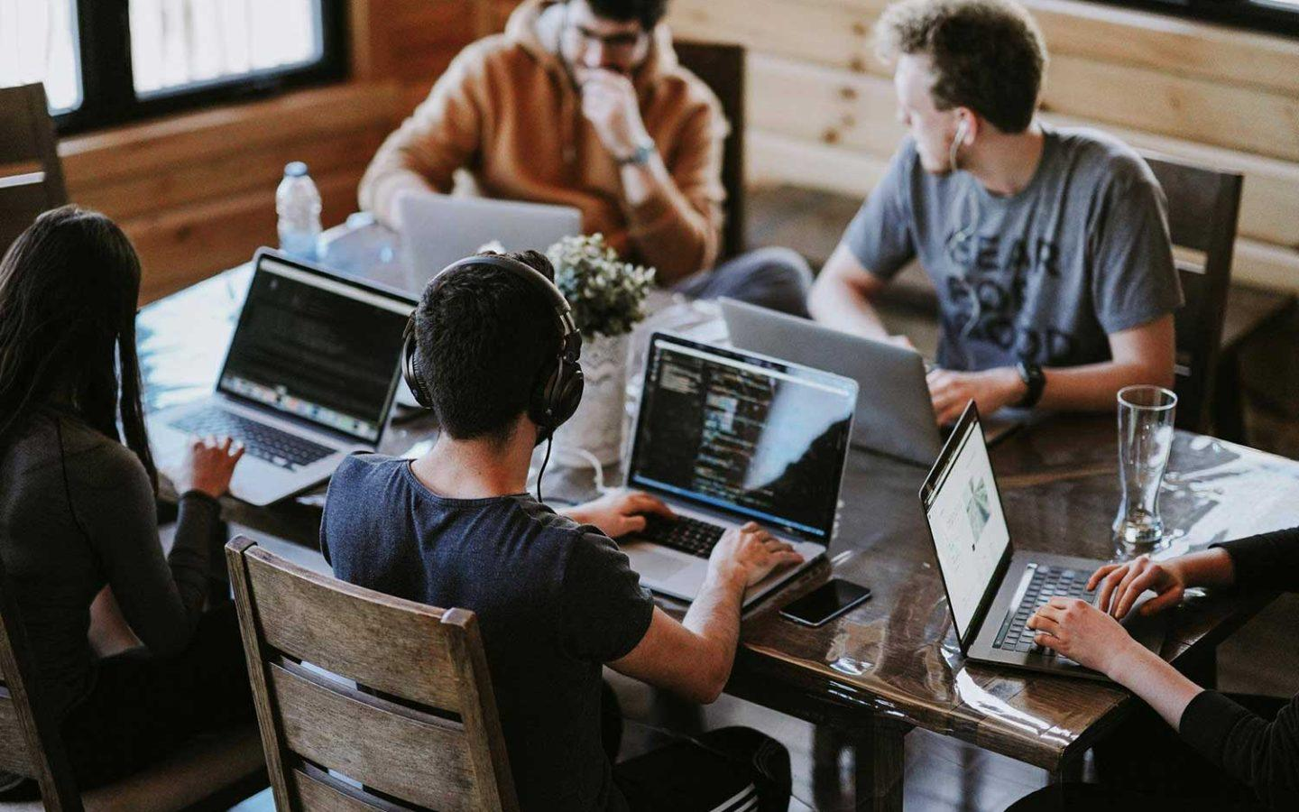 five people with laptops sitting around large desk